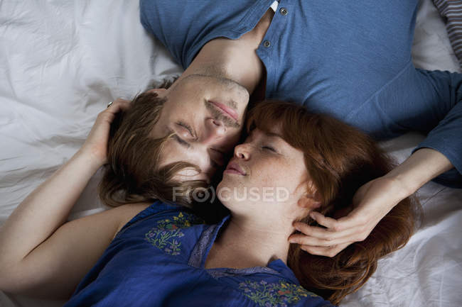A young couple lying head to head on a bed, eyes closed — Stock Photo