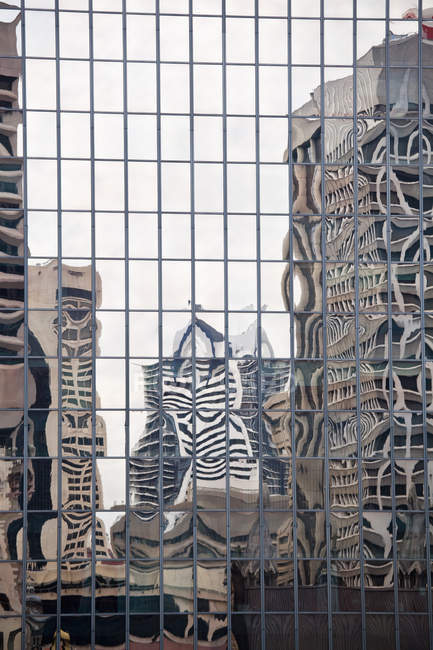 Buildings reflected in mirrored windows of office building facade — Stock Photo