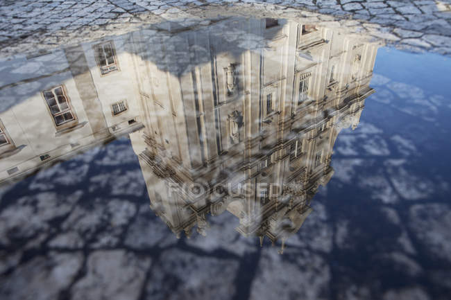 Reflection of Cathedral facade in paddle on paved street — Stock Photo