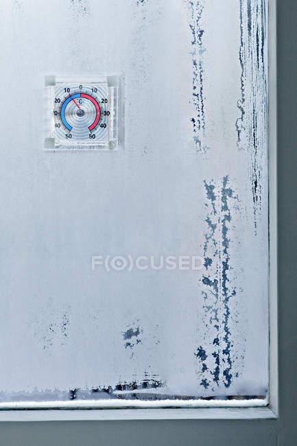 Eiskristalle auf Fenster und Temperaturanzeiger — Stockfoto