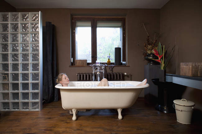 Uma mulher tomando um banho de espuma em uma banheira de pé de garra — Fotografia de Stock