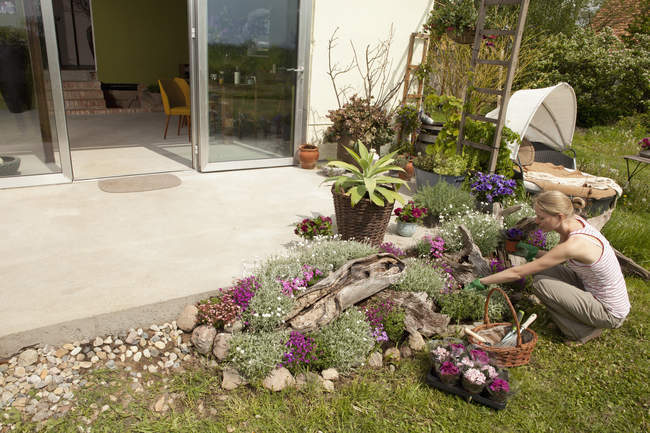 Uma mulher jardinagem em seu quintal, vista de alto ângulo — Fotografia de Stock