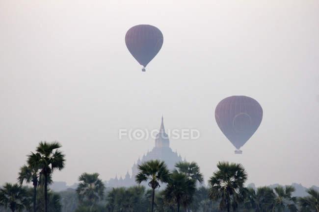 Aerostati di aria calda nel cielo di Bagan con tempio sullo sfondo, Birmania — Foto stock