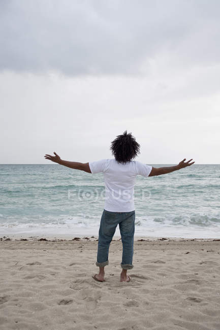 Rückansicht des jungen Mann am Strand mit ausgestreckten Armen — Stockfoto