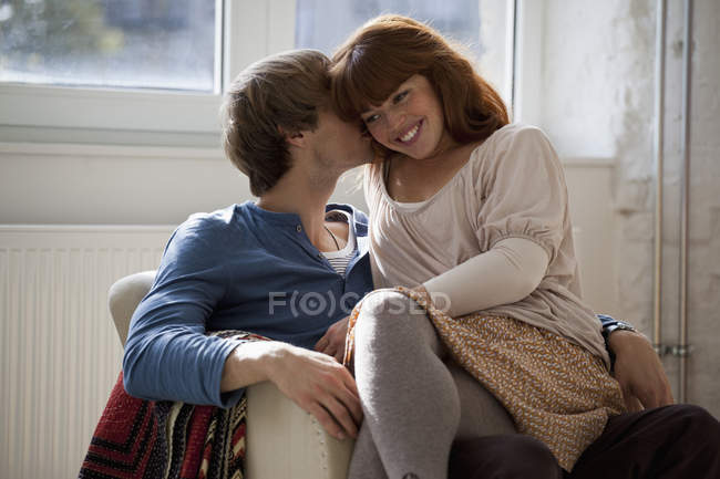 A young man kissing his girlfriend who's sitting on his lap — Stock Photo