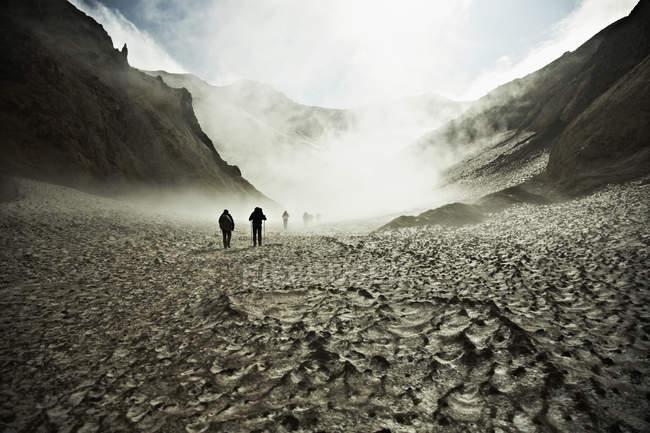 Siluetas de los excursionistas de trekking a través de pradera árida - foto de stock