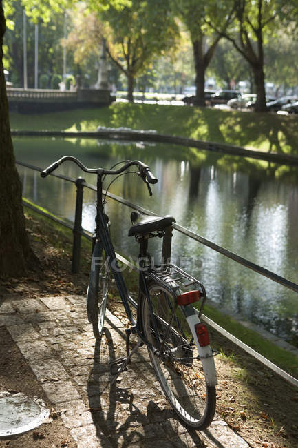 Old fashioned bicycle parked next to a river — Stock Photo