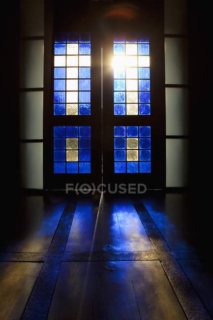 Blue color projected onto floor through stained glass door — Stock Photo