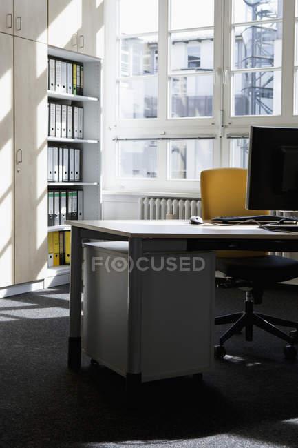 Imagen recortada de un lugar de trabajo vacío y pacífico en la oficina - foto de stock