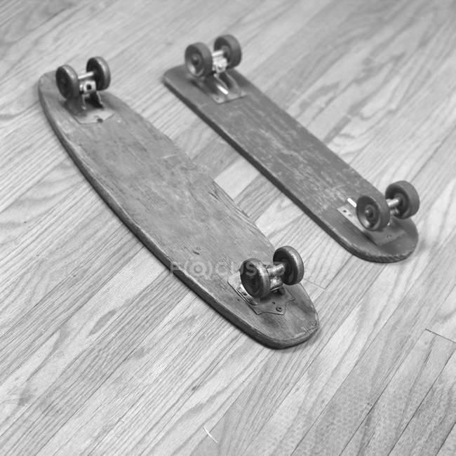 Bouchent la vue de deux vieilles planches à roulettes en bois côte à côte sur le sol — Photo de stock