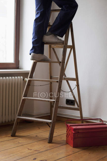 Low section of man standing on a ladder — Stock Photo