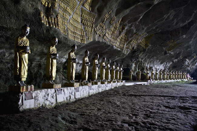 Rows of Buddha statues in ancient cave — Stock Photo