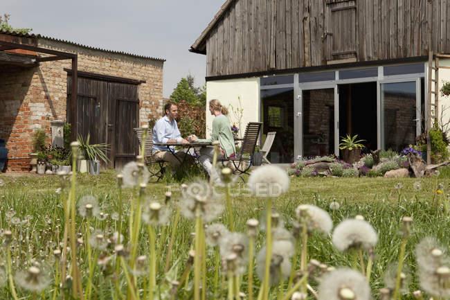 Пару сидить за столом в їх дворі говорити — стокове фото