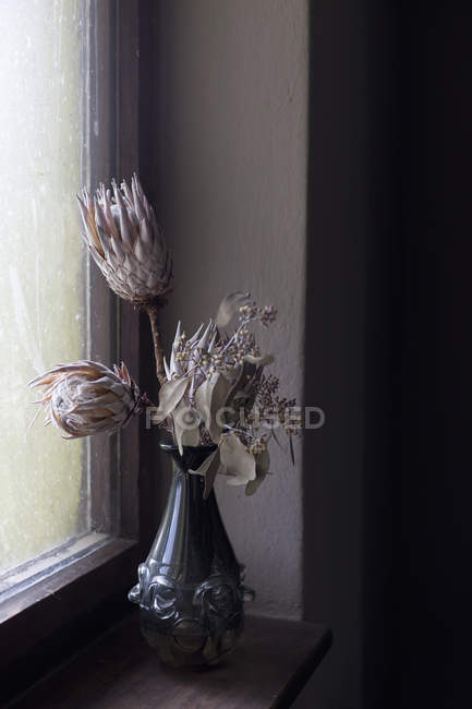 Dried flowers in vase on window sill — Stock Photo