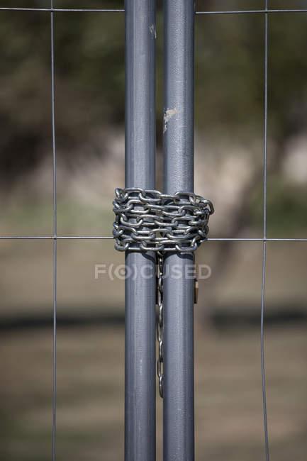 Деталь зв'язали ланцюг на металеві ворота — стокове фото