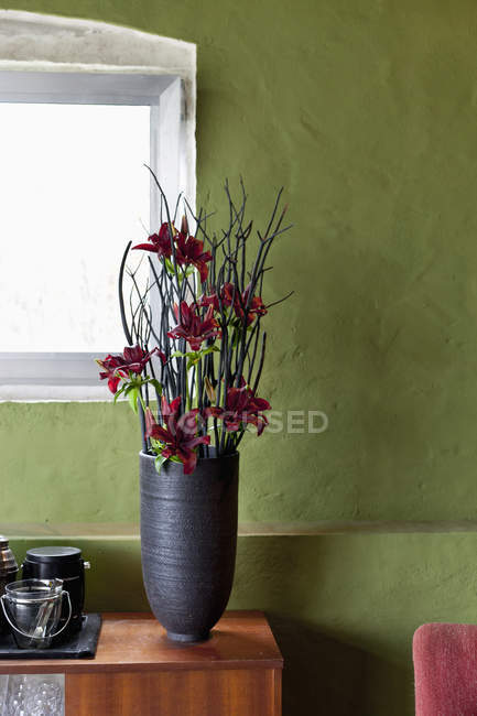 Vase of red flowers on sideboard — Stock Photo