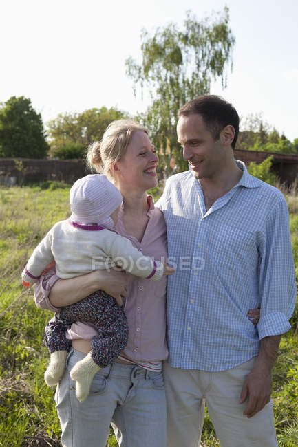 A man and a woman holding a baby standing in their backyard — Stock Photo