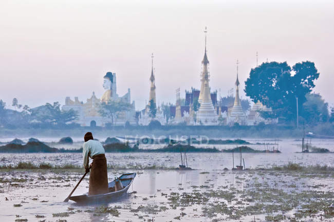 Man rowing boat towards temple on shore — Stock Photo