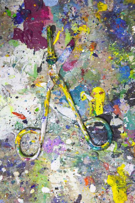 Full frame shot pf splattered paint on scissors — Stock Photo