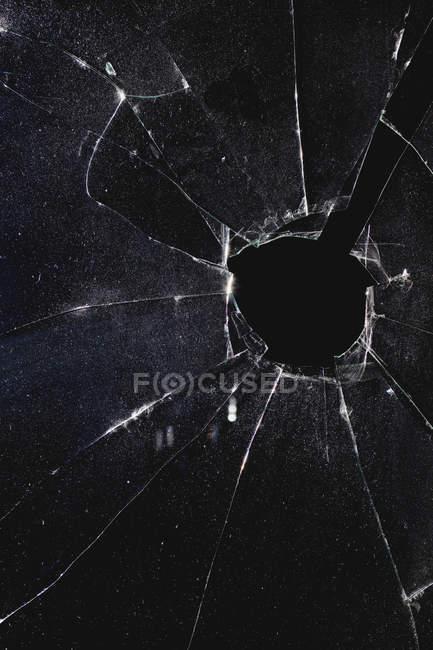Вікно з отвором порушена через скло вночі — стокове фото