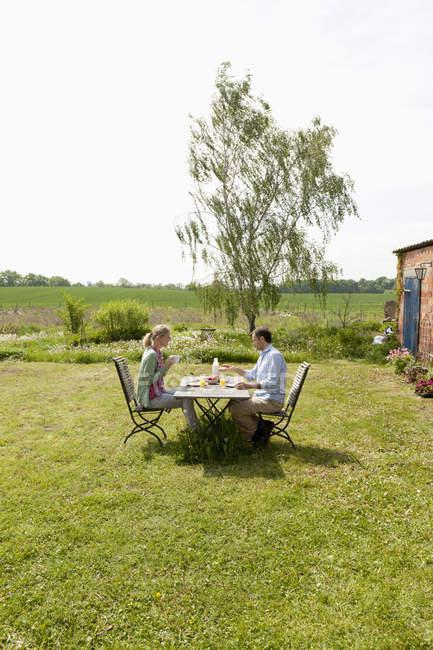 A couple having breakfast in their backyard — Stock Photo