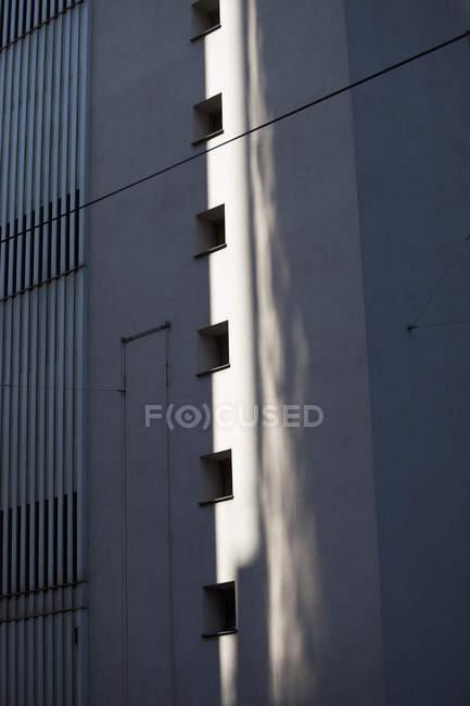 Reflexão da luz projetada na parede ao lado da sequência de furos de janela — Fotografia de Stock