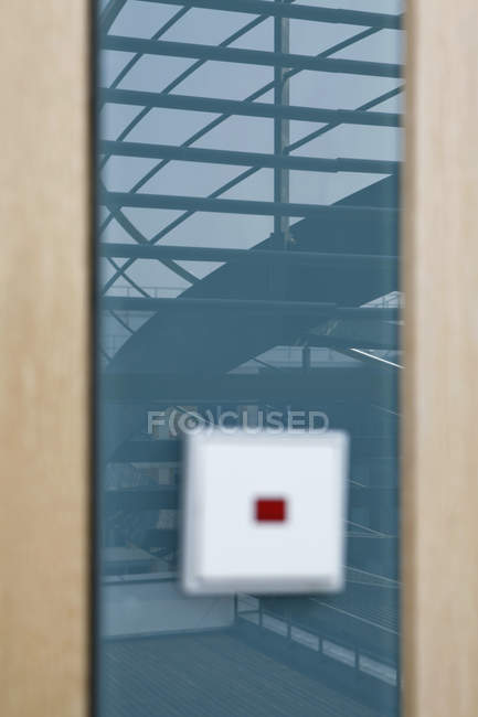 Staircase reflected on glass wall with blurred light switch — Stock Photo
