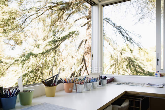 Small office with pots of assorted pens and pencils — Stock Photo