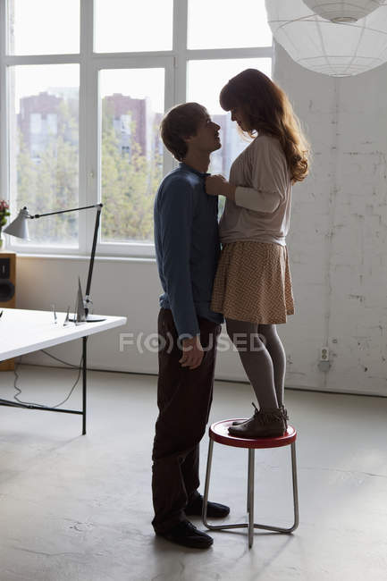 A young woman standing on a stool facing her tall boyfriend — Foto stock