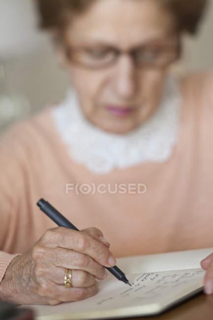 Закри старший жінка писати в Блокноті — стокове фото