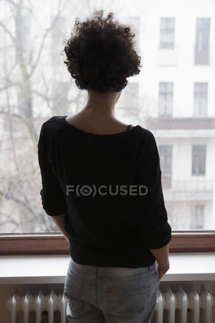 Vista posteriore della donna che guarda attraverso la finestra a casa — Foto stock