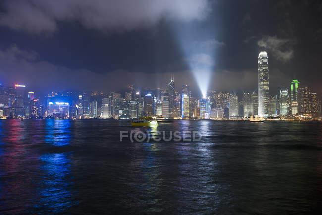 Cityscape iluminado através da água durante a noite, Hong Kong, China — Fotografia de Stock