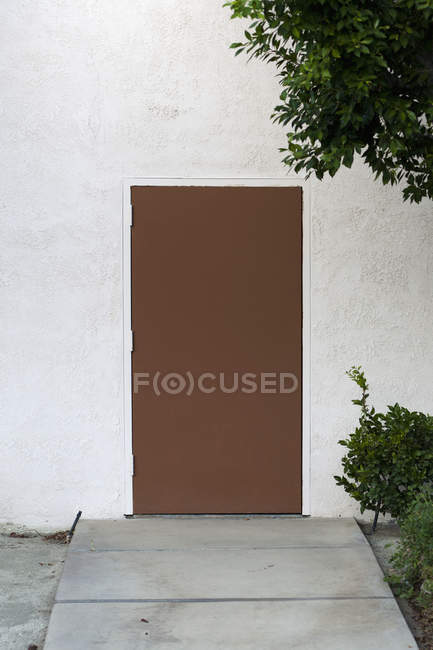 Exterior of wall with plain brown door — Stock Photo