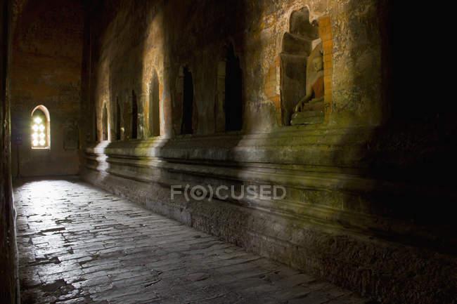 Buddha statues in dark corridor's walls at temple — Stock Photo