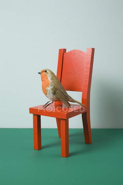 Doté en personnel oiseau assis sur chaise miniature — Photo de stock