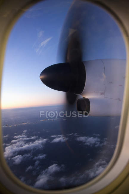 Moving airplane propeller seen through airplane window — Stock Photo
