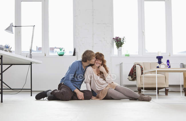 Молодой человек целует свою девушку, бок о бок, сидя на полу — стоковое фото