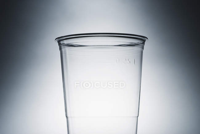 Empty clear plastic cup over gradient grey backdrop — Stock Photo