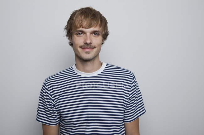 Un jeune homme branché en t-shirt rayé — Photo de stock