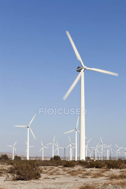 Wind turbines in arid landscape over clear sky — Stock Photo