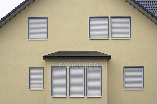 Side of house with window shutters down — Stock Photo