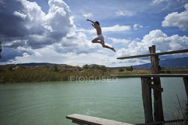 Side view of young boy in midair while jumping in lake — Stock Photo