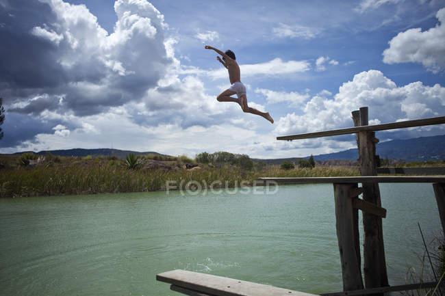 Vista lateral del joven en el aire mientras salta en el lago - foto de stock