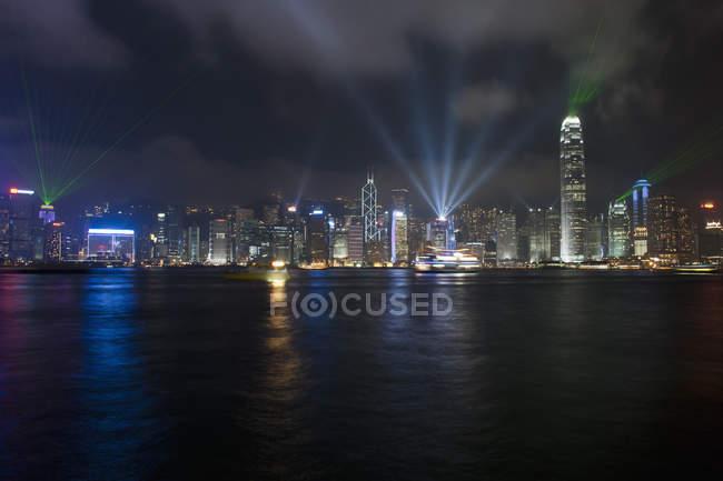 Paisagem urbana de iluminados Hong Kong visto da água à noite — Fotografia de Stock
