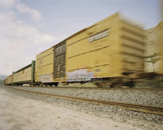 Freight train in motion on arid countryside — Stock Photo