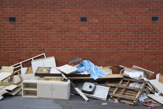 Broken furniture and scraps of garbage piled up against brick wall — Stock Photo