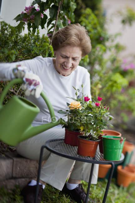 Smiling senior woman gardening outdoors — Stock Photo