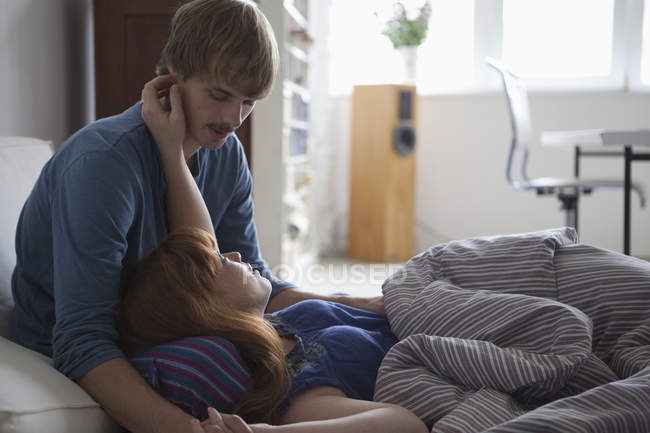 A young couple lying in bed talking and being affectionate — Stock Photo