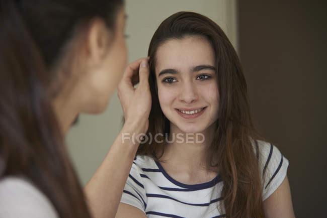 Посміхається дівчина балує люблячою матір'ю в домашніх умовах — стокове фото