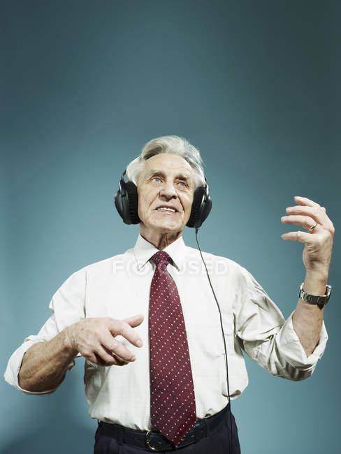 Senior trägt Kopfhörer und spielt Luftgitarre — Stockfoto
